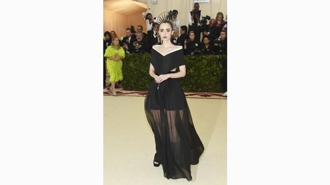 Lily Collins terlihat 'suci' dalam tampilan gothic-nya. Dia memakai gaun off shoulder dan gaun panjang dengan tambahan rok sheer yang mengembang. Gaun ini merupakan karya dari Givenchy. (Jamie McCarthy/Getty Images/AFP)