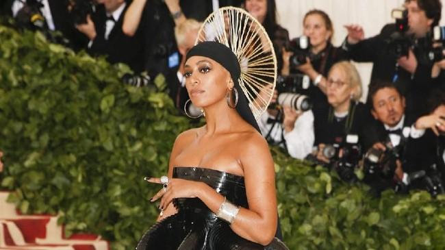 Solange Knowles tampil dengan gaya gaun balon celestial. Headpiece-nya menyerupai lingkaran penuh 'halo' dari Shani Crowe berwarna emas. (REUTERS/Carlo Allegri)
