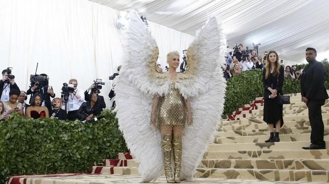 Statement yang tak kalah mencolok dikenakan Katy Perry lewat mini dress keemasan dari Versace, boot tinggi, dan sayap malaikat berukuran besar yang disebut berukuran 1,8 meter. (REUTERS/Eduardo Munoz)