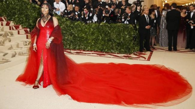 Dengan gaun ombre merah Oscar de la Renta, Nicki Minaj melengkapi tampilannya dengan cape dan headpiece kristal, serta salib merah mungil. (REUTERS/Carlo Allegri)