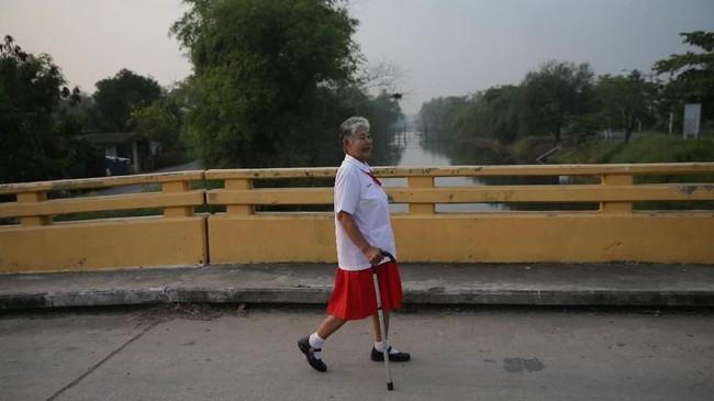 Somjit Teeraroj, 77, berjalan menuju pemberhentian bus di Ayutthaya, Thailand.