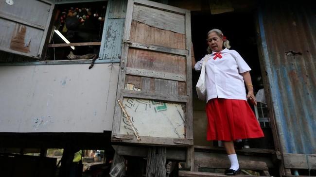 Poonsri Seangnual, 63, dengan berseragam meninggalkan rumahnya di Ayutthaya, Thailand, untuk pergi ke sekolah lansia di Chiang Rak Noi.