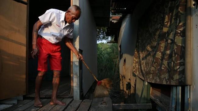 Choochart Supkerd, 63, yang belajar di sekolah lansia, sedang membersihkan rumahnya di Ayutthaya, Thailand. Ia mengikuti kursus 12 pekan yang disebutnya sebagai obat mujarab mengatasi stress. Sekolah adalah tempatnya mencari teman. (REUTERS/Athit Perawongmetha)