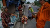Somjit Teeraroj (C), 77, yang belajar Sekolah Lansia menawarkan sumbangan pada seorang biksy Budha dekat rumahnya di Ayutthaya, Thailand. Somjit bercerita, ketika suaminya meninggal karena kecelakaan, dia lalu hidup sendirian. Bersekolah adalah caranya untuk mengatasi kesedihan. (REUTERS/Athit Perawongmetha)