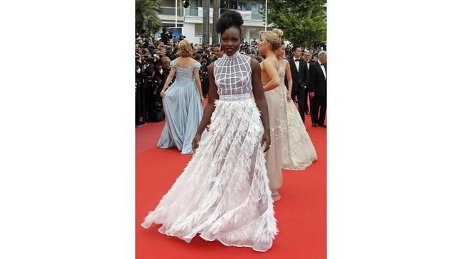 Melewatkan keriuhan Met Gala pekan lalu, aktris Lupita Nyong'O justru hadir membuat kejutan di pemutaran film 'Sorry Angle', di Festival Film Cannes 2018. Mengenakan gaun serba putih Dior Haute Couture dengan aksen di bagian dada membuat tampilannya mengesankan. (REUTERS/Regis Duvignau)