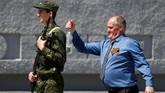 Seorang peserta menyemprotkan air pada seorang penjaga sebelum meletakkan karangan bunga di memorial Perang Dunia II di Stavropol, Rusia. (REUTERS/Eduard Korniyenko)