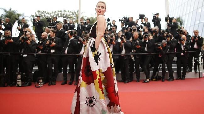 Masih di pemutaran film 'Sorry Angle', aktris Amber Heard mengenakan busana bold Valentino, dengan motif ukuran besar yang mencolok mata. Aksinya tak pelak membuat sorot kamera tak berhenti memotretnya. (REUTERS/Stephane Mahe)