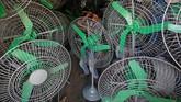 Seorang teknisi menggunakan palu untuk membenarkan kap besi kipas angin elektrik di dalam sebuah toko di Mumbai, India. (REUTERS/Francis Mascarenhas)