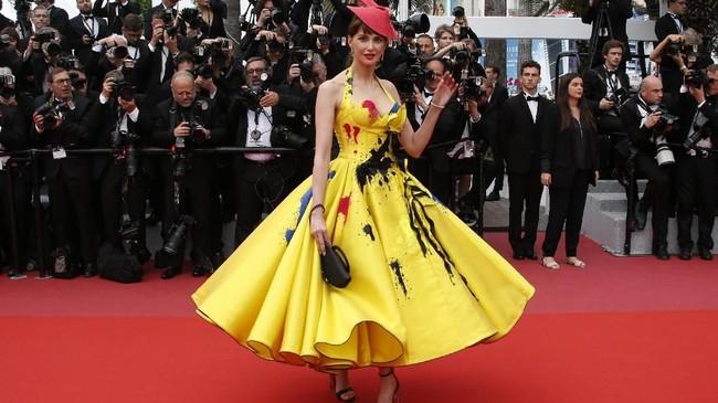 Gaun yang dikenakan Frederique Bel ini tak hanya mencolok karena warna kuning menyalanya tapi juga kesan tumpahan cat dan topi merah. Sekilas gaun ini akan mengingatkan pada busana ikonis dalam peragaan busana Alexander McQueen. (REUTERS/Jean-Paul Pelissier)
