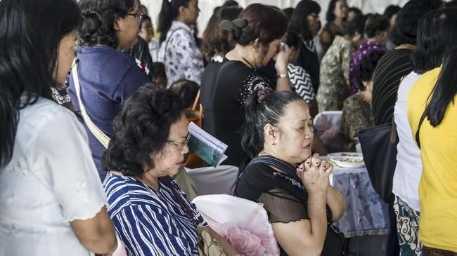 Para kerabat dari Martha Djumani berkumpul untuk berkabung atas kematian perempuan tersebut dalam teror bom di Gerja Pantekosta, Surabaya, 13 Mei 2018.(AFP PHOTO / JUNI KRISWANTO)