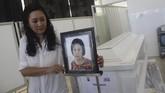 Maria Hamdani, memasang foto bibinya, Mayawati di Rumah Persemayaman Gotong Royong, Malang, Jawa Timur, Senin (14/5). Tercatat hingga Senin (14/5) petang jumlah korban jiwa dalam rentetan teror bom di Surabaya mencapai 25 orag--13 pelaku, sisanya warga. (ANTARA FOTO/Ari Bowo Sucipto)
