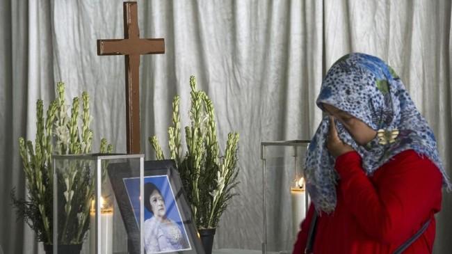 Seorang perempuan mengelap air mata tanda kesedihannya atas kematian Sri Puji yang menjadi salah satu korban rentetan teror bom di Surabaya, 13 Mei 2018. (AFP PHOTO / JUNI KRISWANTO)