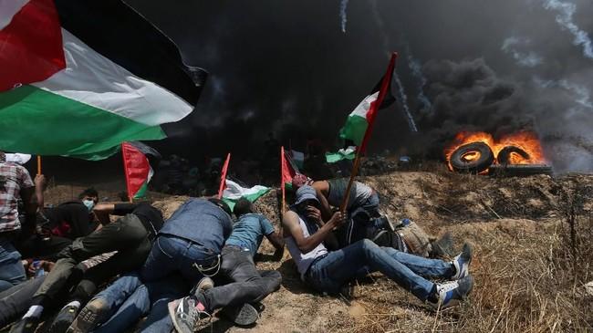 Aksi tanpa senjata itu direspons dengan berondongan peluru dan hujan gas air mata dari aparat Israel.(REUTERS/Ibraheem Abu Mustafa)