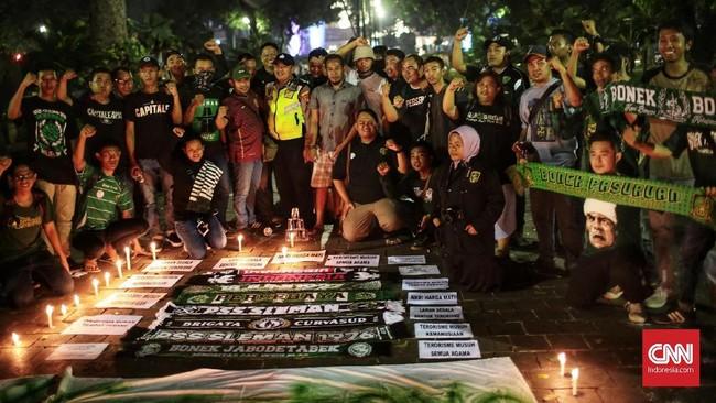 Sejumlah Bonek foto bersama seorang polisi yang menjaga aksi simpati untuk korban bom Surabaya di Taman Suropati, Jakarta. (CNN Indonesia/Andry Novelino)