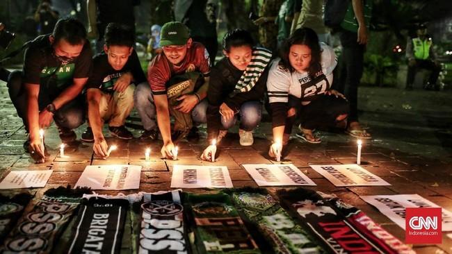 Sejumlah Bonek menyalakan lilin sebagai aksi simpati. Total ada 25 orang meninggal karena aksi teror bom di Surabaya dan Sidoarjo. (CNN Indonesia/Andry Novelino)