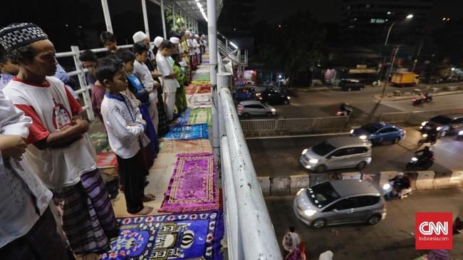 Tak hanya memanfaatkan jalanan di sela-sela ruko tempat jualan, sejumlah warga kawasan Pasar Gembrong, Jakarta juga tampak menjalankan salat tarawih pertamanya di jembatan penyeberangan orang. (CNN Indonesia/Adhi Wicaksono)