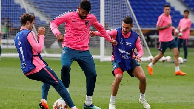 Striker AtleticoMadrid Diego Costa, berusaha melewati dua rekannya pada sesi latihan. Costa berambisi meraih trofi Liga Europa pertamanya. (REUTERS/Christian Hartmann)