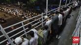 Deretan orang dalam susunan saf yang rapih di JPO Pasar Gembrong, Jakarta berupaya khusyuk menjalankan salat tarawih di antara suasana jalanan dan kendaraan yang riuh. (CNN Indonesia/Adhi Wicaksono)