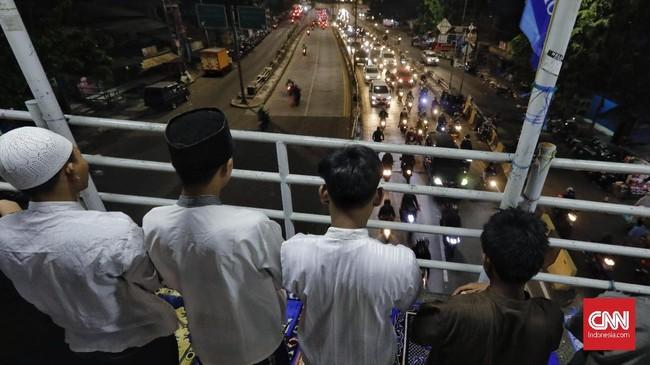 Di antara riuh jalanan, suara mesin kendaraan, beberapa orang tampak tetap khusyuk menjalankan salat tarawih di atas jembatan penyeberangan, di kawasan Pasar Gembrong.(CNN Indonesia/Adhi Wicaksono)