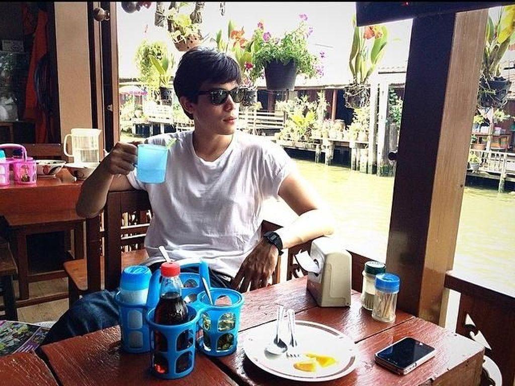 Bergaya kasual, Sunny sedang menunggu makanan pesanannya disiapkan di sebuah restoran. Kacamata hitam sepertinya jadi aksesoris andalan Sunny ya? Foto: Instagram sunny_suwanmethanont