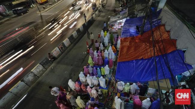 Dipotret dari atas, sejumlah warga tampak tumpah ruah hingga ke jalan dalam menjalankan salat tarawih pertama menjelang bulan puasa Ramadan esok hari di Pasar Gembrong. (CNN Indonesia/Adhi Wicaksono)