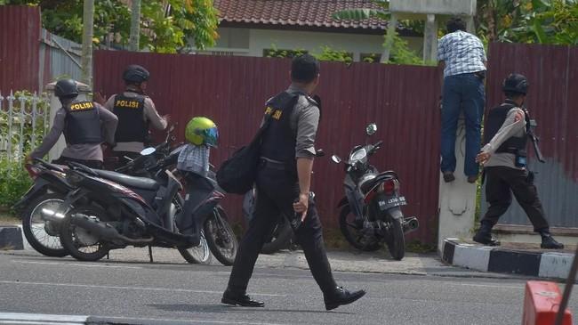 Dua anggota Polda Riau terluka akibat sabetan pedang pelaku. Sementara empat pelaku ditembak mati. Satu oranganggota kelompok teroris berhasil kabur.(AFP PHOTO / WAHYUDI)