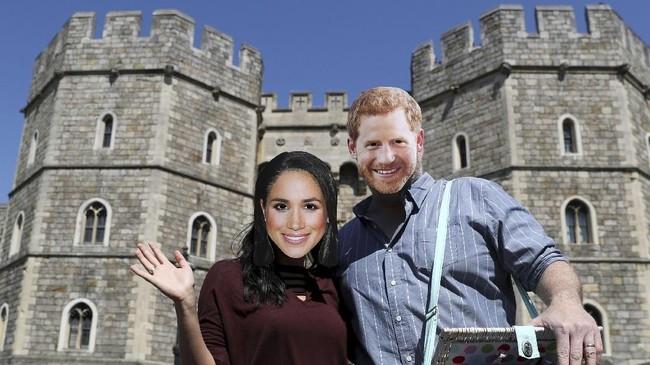 Sepasang pengunjung mengenakan topeng Pangeran Harry dan Meghan Markle di depan Kastel Windsor yang akan menjadi lokasi pernikahan anggota kerajaan itu pada 19 Mei nanti. (Reuters/Marko Djurica)