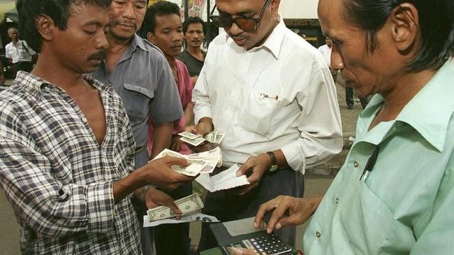 Pengusaha Indonesia membeli dolar AS dari pejalan kaki di jalanan Jakarta pada Juni 1998. Krisis ekonomi mengakibatkan nilai tukar rupiah pada masa itu sempat menyentuh angka Rp16 ribu, sehingga membeli dolar di jalanan lebih murah ketimbang di tempat penukaran uang resmi. (Reuters/RP1DRIGCOCAA)