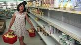 Seorang pelanggan berjalan melewati rak-rak kosong yang biasanya terisi dengan produk olahan susu di sebuah supermarket di Jakarta. Inflasi yang mencapai 60 persen pada 1998 membuat toko-toko di Jakarta kehabisan bahan makanan. (AFP PHOTO Kemal JUFRI)