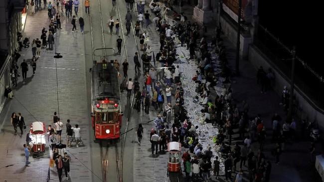 Orang-orang terlihat melipir ke pinggir jalan saat azan Magrib tanda waktu berbuka puasa terdengardi kawasanIstiklal, Istanbul, Turki, Rabu (16/5). (REUTERS/Huseyin Aldemir)