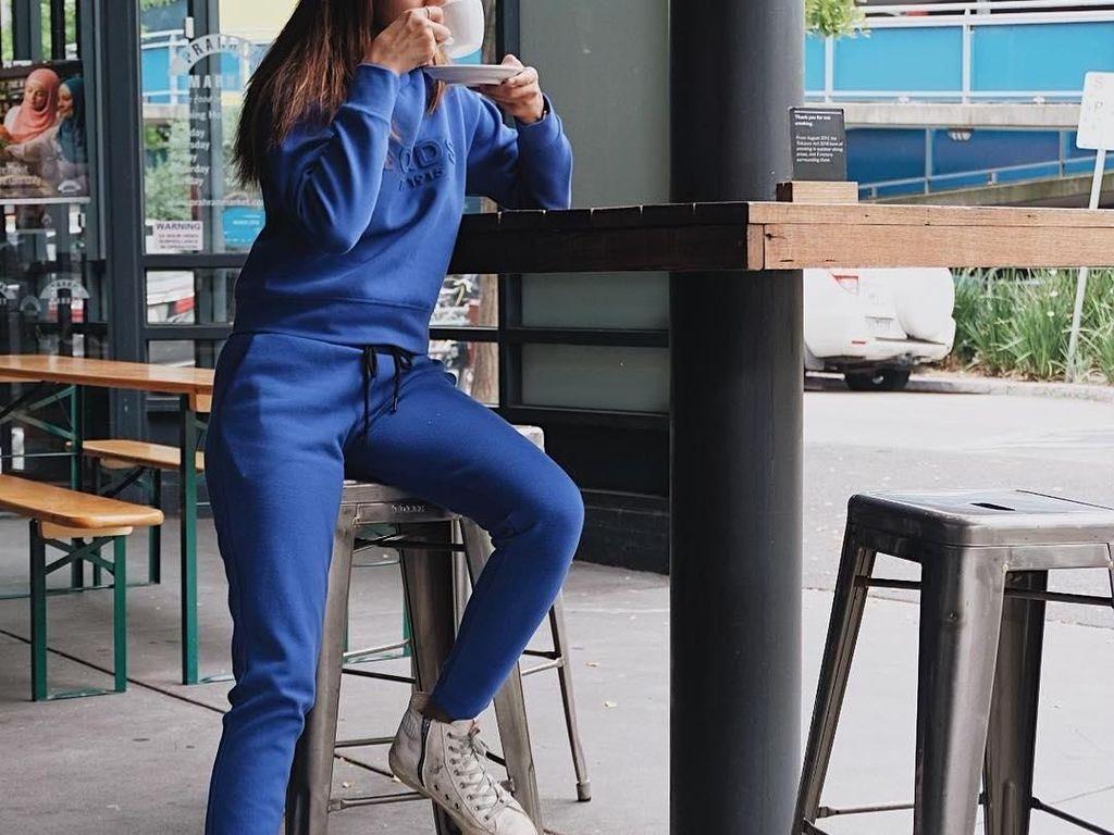 Masih pakai pakaian sporty, Kirana kali ini menyesap kopi di sebuah kafe. Gaya memandang ke depan tanpa lihat kameran bikin pose ngopinya keren! Foto: Instagram kiranalarasati