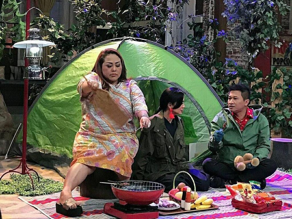 Wah Mbak Nunung lagi piknik nih. Di depan tenda, ia asyik mengipas sate. Sementara makanan di depannya juga ada snack hingga buah segar. Foto: Instagram