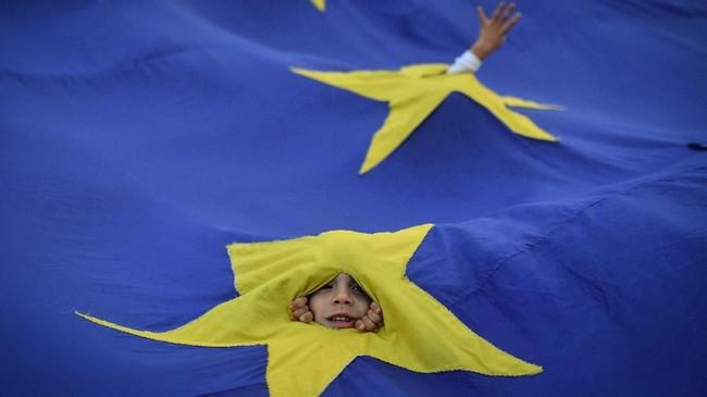 Wajah seorang anak muncul di sela-sela bendera raksasa Uni Eropa pada sebuah demonstrasi di Bucharest menuntut pengunduran diri Perdana Menteri Rumania. (AFP PHOTO / Daniel MIHAILESCU)