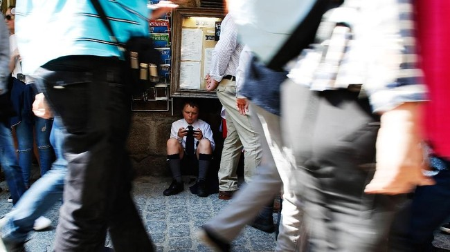 Seorang bocah menatap telepon genggamnya sembari duduk di pinggir jalan, sementara para turis lalu-lalang pada hari yang cerah di Mont-Saint-Michel, di sebelah utara Perancis. (AFP PHOTO / CHARLY TRIBALLEAU)