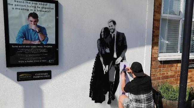 Seniman graffiti, Pegasus, membuat karya seni bertema Royal Wedding di tembok sebuah bar di kawasan Windsor. (REUTERS/Marko Djurica)