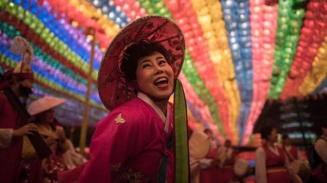Seorang penganut agama Budha menari di bawah lentera-lentera di kuil Jogye. Menyambut perayaan kelahiran Budha yang jatuh pada 22 Mei tahun ini, di Seoul, Korea Selatan, diadakan Festival Lampion Teratai. (AFP PHOTO / Ed JONES)