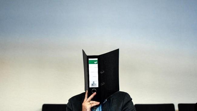Seorang prajurit Jerman yang dituduh melecehkan seorang anak, menyembunyikan wajahnya di balik map kertas sembari menunggu hakim menjatuhkan vonis. Ia kemudian divonis delapan tahun penjara dan denda 12.500 euro yang harus diberikan pada sang anak. (AFP PHOTO / dpa / Patrick Seeger)