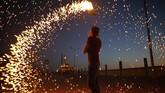 Seorang remaja Palestina melambaikan kembang api dekat suatu mesjid di kota Gaza. Mulai pekan ini umat Islam di Palestina bersiap menjalanai bulan suci Ramadan. (AFP PHOTO / MOHAMMED ABED)