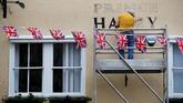 Seorang pekerja mengecat dinding salah satu pub di London dengan tema Royal Wedding Pangeran Harry dan Meghan Markle.(REUTERS/Phil Noble)