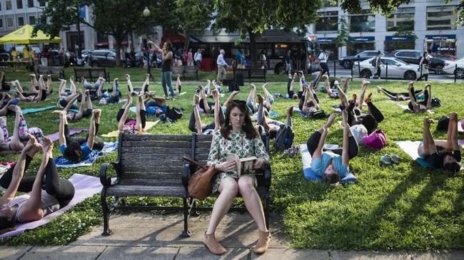 Seorang perempuan duduk di bangku dan asik membaca sementara di sekelilingnya orang-orang sedang mengikuti kelas Yoga di sebuah taman di Washington DC, Amerika Serikat. (AFP PHOTO / Andrew CABALLERO-REYNOLDS)