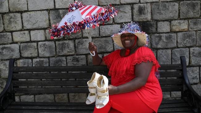 Adinas Perkins dari New Orleans yang berpose membawa sepatu pernikahan, mengaku melihat sosok Pangeran Charles dan Putri Diana di dalam diri Pangeran Harry dan Meghan Markle. Itulah yang membuatnya tak mau melewatkan pernikahan yang satu ini. (REUTERS/Marko Djurica)