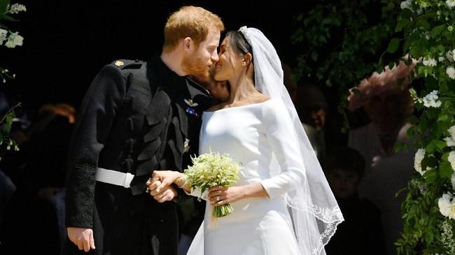 Setelah sah sebagai suami istri, Pangeran Harry dan Meghan Markle keluar dari St. George dan berciuman di tangga gereja sebelum menaiki kereta kencana yang ditarik kuda. (Ben Birchall/Pool via REUTERS)