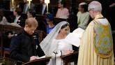 Harry dan Markle lalu sama-sama mengucap janji pernikahan. Seisi ruangan juga ditanya apakah ada yang keberatan dengan pernikahan mereka. Jawabannya hening. (Dominic Lipinski/Pool via REUTERS)