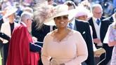 Oprah Winfrey datang dengan busana pink dan topi, sesuai dress code bahwa semua wanita yang datang ke pernikahan harus mengenakan topi seperti kekhasan Kerajaan Inggris. (Ian West/Pool via REUTERS)