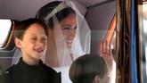 Meghan Markle tiba di Kapel St. George, Kastel Windsor di mana ia akan menjalani pemberkatan untuk pernikahannya dengan Pangeran Harry, Sabtu (19/5). Ia menumpang mobil ditemani dua pengiring pengantin cilik. Chris Radburn/Pool via REUTERS)