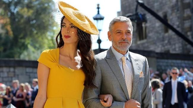 Amal Clooney yang datang bergandengan dengan suaminya George Clooney tampak cantik dengan gaun dan topi kuning. George Clooney sendiri mengenakan setelan jas abu-abu. (Gareth Fuller/Pool via REUTERS)