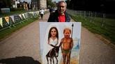 Kaya Mar, warga London sampai membawa lukisannya untuk berpose di Windsor. Menurutnya, pernikahan Harry Markle bisa membuat warga Inggris lupa sejenak pada berbagai masalah mereka, seperti Brexit. (REUTERS/Damir Sagolj)