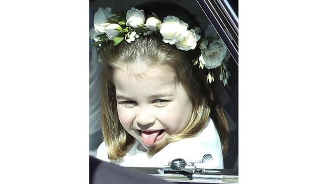 Tak cukup mencuri perhatian dengan caranya mengangkat kaki, Putri Charlotte juga terlihat menggemaskan saat dia menjulurkan lidahnya dengan nakal dari dalam mobil. (Andrew Milligan/Pool via REUTERS)