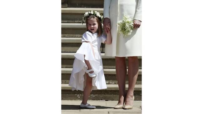 Sedangkan Putri Charlotte memakai gaun putih dengan mahkota bunga di kepalanya. (Jane Barlow/Pool via REUTERS)