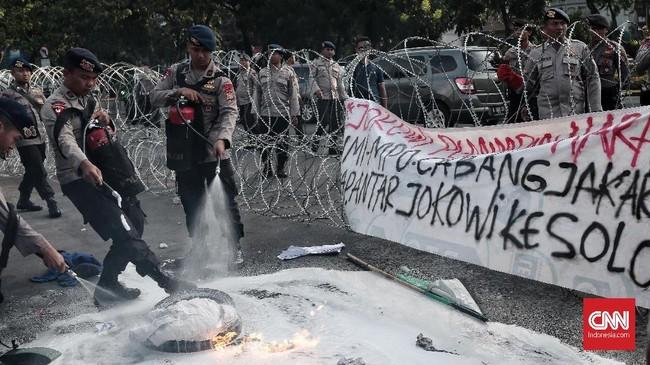 Polisi berupaya memadamkan api yang membakar ban yang dibawa paramahasiswa pelaku aksi Refleksi 20 tahun Reformasi.(CNN Indonesia/Andry Novelino)